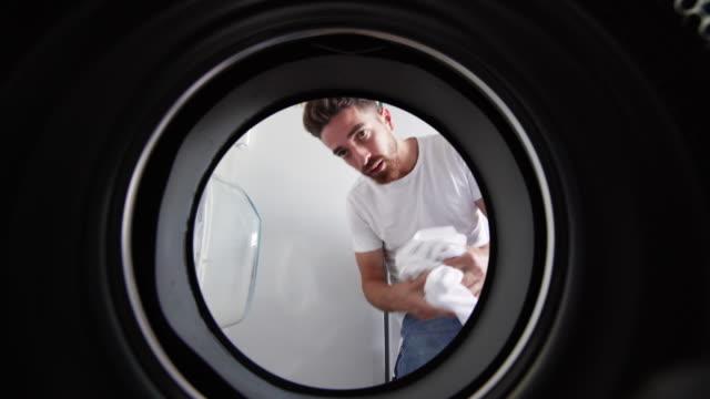 pov young man adding clothes to washing machine - caricare attività video stock e b–roll