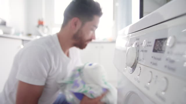 CU Young man adding clothes to washing machine