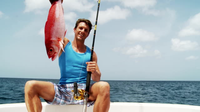young man admires his fish - snapper fish stock videos & royalty-free footage