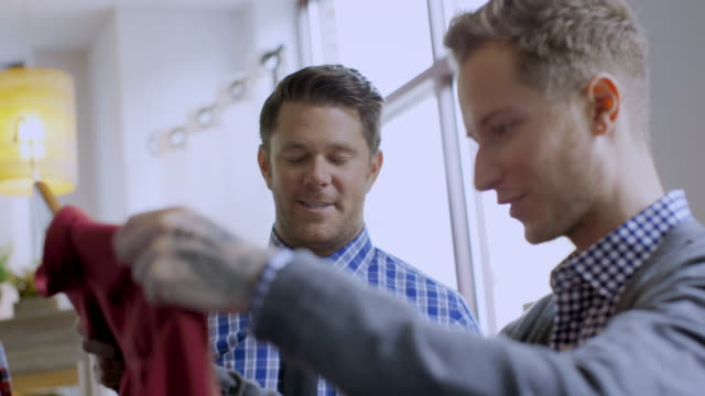 Young man admires shirt in clothing shop, store manager offers advice and assistance and closes the deal
