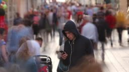 Young Man Alone in Busy Street