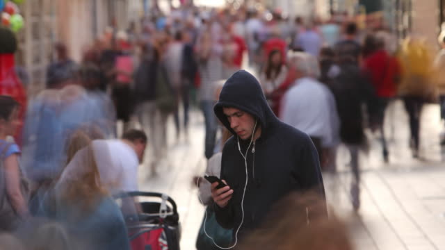 young man alone in busy street - portability stock videos & royalty-free footage