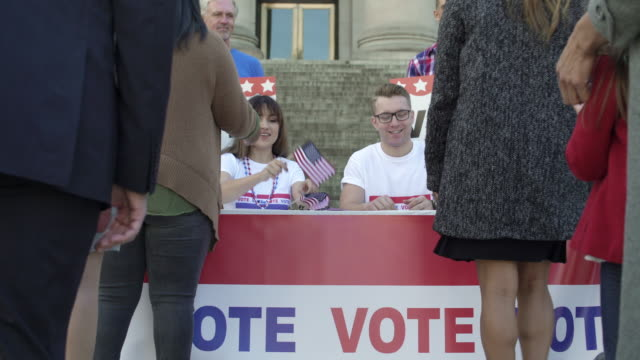 a young man and a woman dispensing flags at a political rally - voting stock videos & royalty-free footage