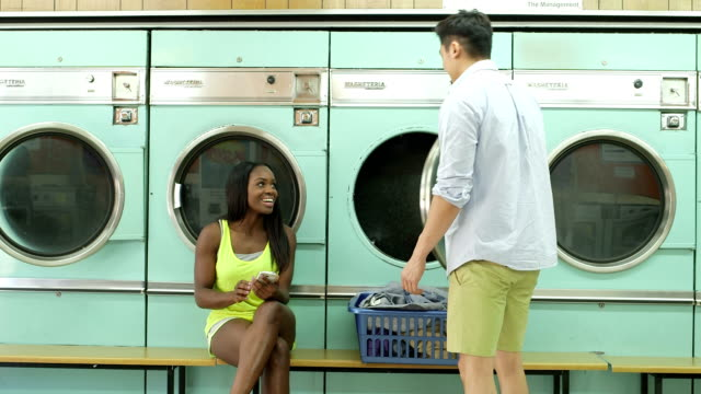 mls a young man and a young woman meet in a launderette - waschsalon stock-videos und b-roll-filmmaterial
