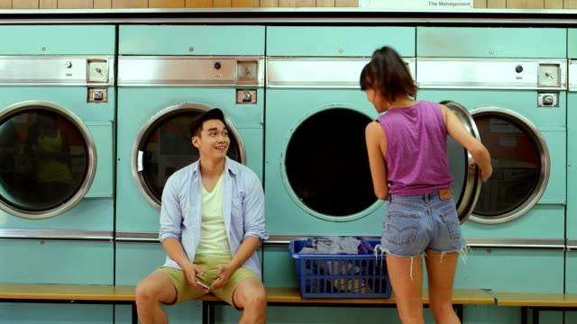 mls a young man and a young woman meet in a launderette - 輪っかのイヤリング点の映像素材/bロール