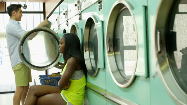 stockvideo's en b-roll-footage met mls a young man and a young woman meet in a launderette - wasmand