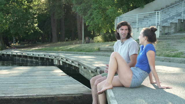 A young man and a young woman sitting on side of a lake