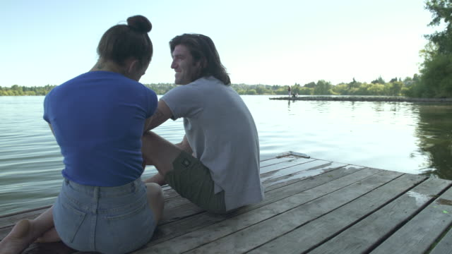 A young man and a young woman talking on a dock