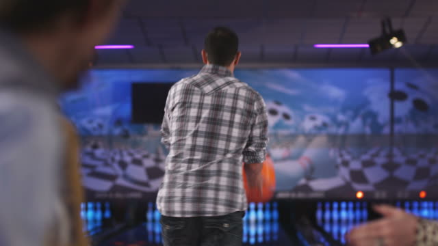 young man and friends at a bowling alley - ボウリング点の映像素材/bロール