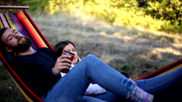 young man and girl in orange hammock from back in beautiful forest - dorso umano video stock e b–roll