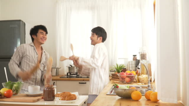young man and roommate have fun dancing in the modern kitchen after they wake up in morning