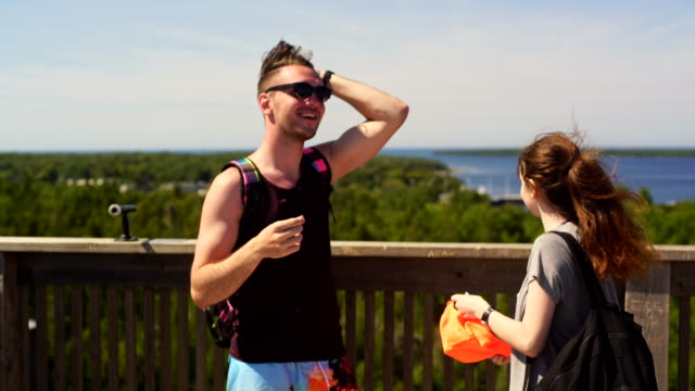 Young man and teenager girl observe Huron Lake from tower