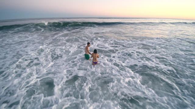 夕暮れ時の海で泳ぐ男と 10 代の若い女の子は、サーフィンの波がヒットを取得します。ハンプトンビーチ、ロングアイランド、ニューヨーク州、アメリカ合衆国。低高度空撮。 - ロングアイランド点の映像素材/bロール