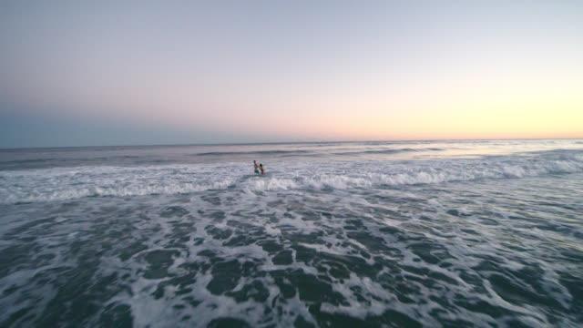 vídeos y material grabado en eventos de stock de hombre y adolescente niña nadando en el océano al atardecer recibe golpes por las olas en el surf. playa de hampton, long island, nueva york estado, estados unidos. - long island