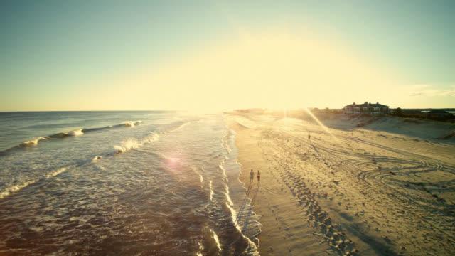 若い男と 10 代女の子一緒にウォーキングとロングアイランドのビーチで話す空中映像。 - ロングアイランド点の映像素材/bロール