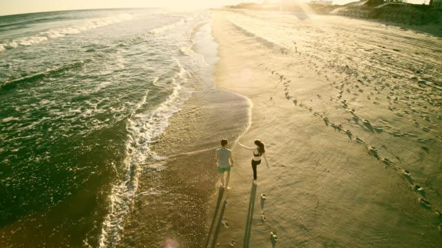 vídeos y material grabado en eventos de stock de hombre y adolescente joven caminando juntos y hablando en la playa de long island. imágenes aéreas con cámara subiendo desde muy baja altura a la vista directamente encima. - long island