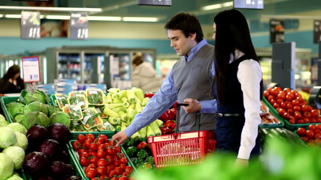 Young man and woman buying vegetable