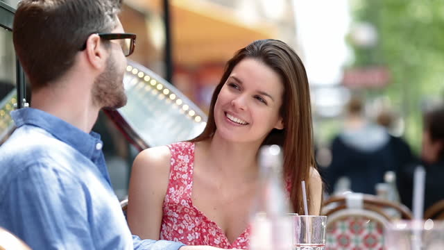 young man and woman chat over drinks at parisian sidewalk cafe. - dining stock videos & royalty-free footage