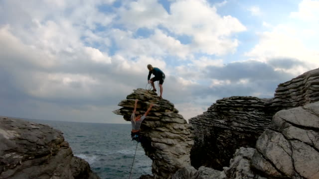 young man and woman climb rock sea-stack, using rope and gear - rope stock videos & royalty-free footage