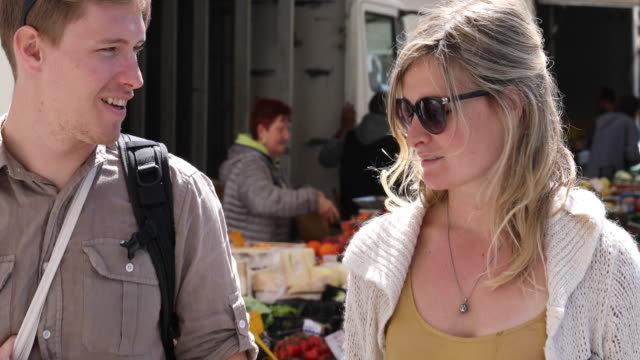 young man and woman communicate near market - market stall stock videos & royalty-free footage