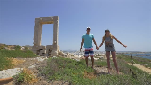 a young man and woman couple jumping in front of ancient ruins of the apollo temple, traveling in naxos, greece, europe. - naxos greek islands stock videos & royalty-free footage