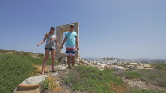 a young man and woman couple jumping in front of ancient ruins of the apollo temple, traveling in naxos, greece, europe. - slow motion - naxos greek islands stock videos & royalty-free footage