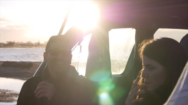 a young man and woman couple sitting in the back of an suv car. - slow motion - boys stock videos & royalty-free footage