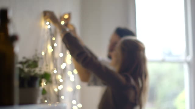 young man and woman decorating wall with lights during christmas - hanging stock videos & royalty-free footage