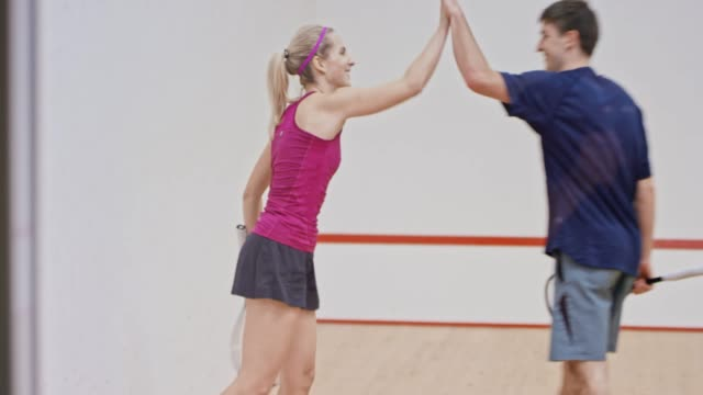 young man and woman doing high five after finishing a game of squash - squash sport stock videos & royalty-free footage