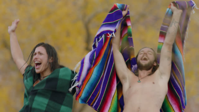vídeos de stock e filmes b-roll de young man and woman draped in towels jump and cheer after invigorating swim on camping trip. - ecstatic