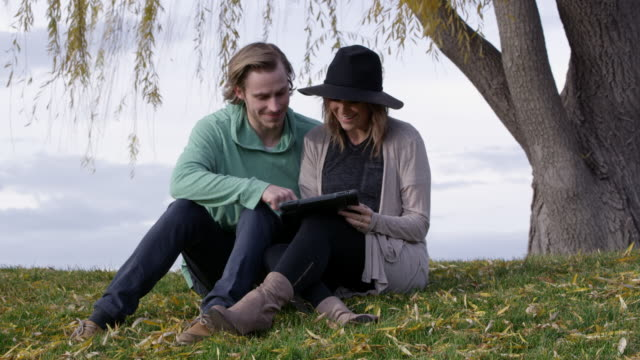 Young man and woman drawing on tablet and laughing