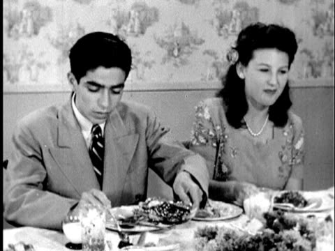 1945 b/w ms young man and woman eating at dinner party; narration asking audience about their manners; cu young man's hands cutting meat on plate / united states / audio - gutes benehmen stock-videos und b-roll-filmmaterial