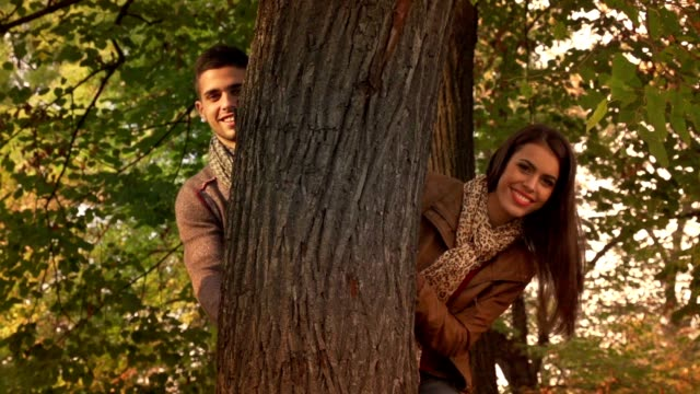 young man and woman enjoying autumn day in the park. - hide and seek stock videos & royalty-free footage
