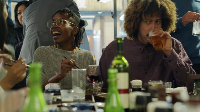 ung man och kvinna njuter av mål tid med vänner i restaurang i tokyo - ölglas bildbanksvideor och videomaterial från bakom kulisserna