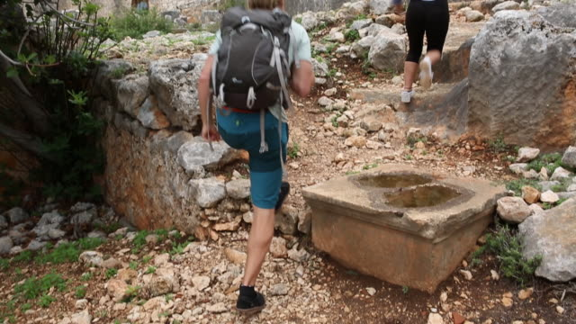 young man and woman explore ruins on hillside - pedal pushers stock videos & royalty-free footage