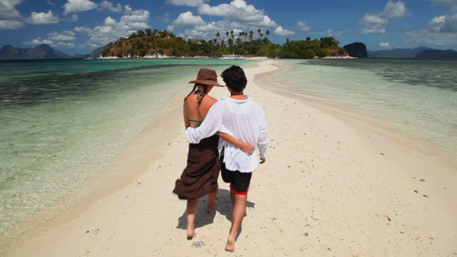 ws young man and woman having a romantic walk on idyllic sandbar towards tropical island in background / snake island, bacuit archipelago, el nido, palawan, philippines - philippines stock videos & royalty-free footage