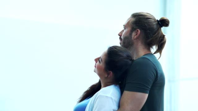 vídeos y material grabado en eventos de stock de joven hombre y mujer abrazándose de pie en casa - esposo