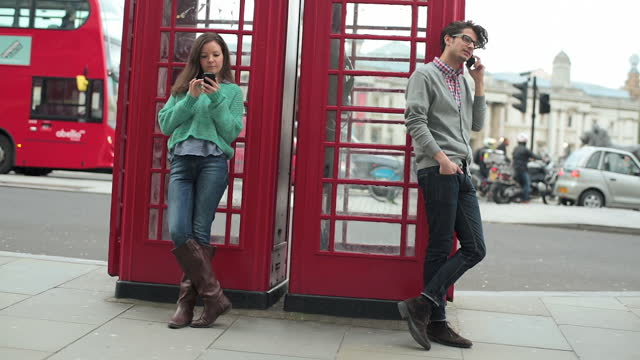 Two young people use their cell phones next to phone booth.