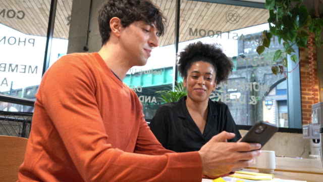 young man and woman looking at mobile phones in open plan office - portability stock videos & royalty-free footage