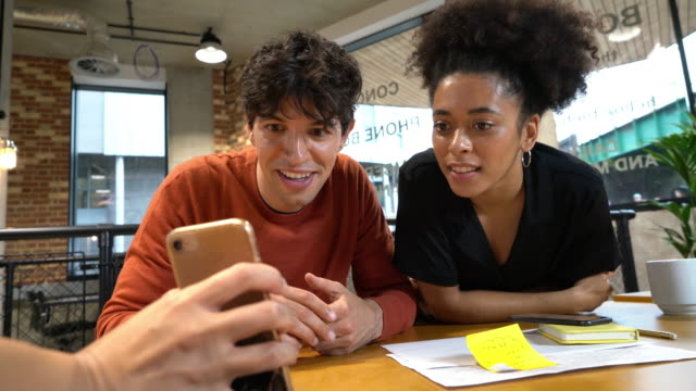 young man and woman looking at mobile phones in open plan office - smart casual stock videos & royalty-free footage
