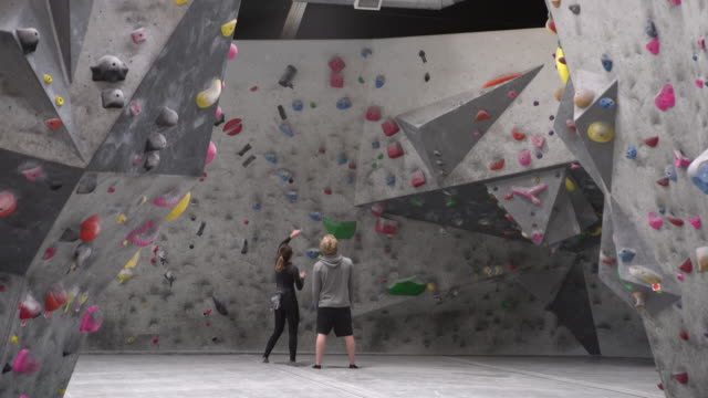 ws young man and woman looking up at a climbing wall - climbing wall stock videos & royalty-free footage