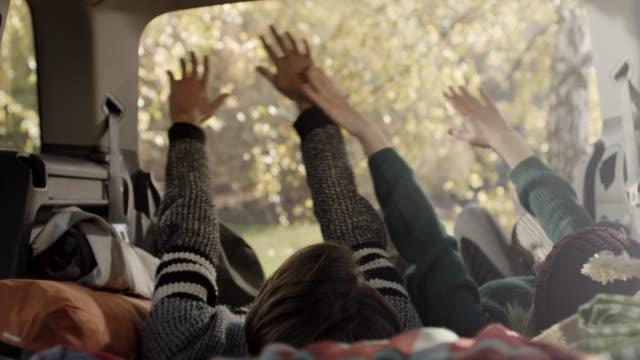 vídeos de stock, filmes e b-roll de jovem e mulher deitada na parte de trás do carro e levantando as mãos no ar - de braço levantado