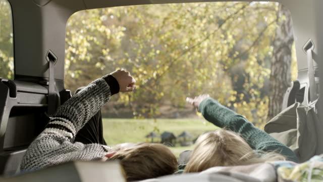 vídeos de stock, filmes e b-roll de jovem e mulher deitada no carro e apontando com os dedos na natureza - reclinando