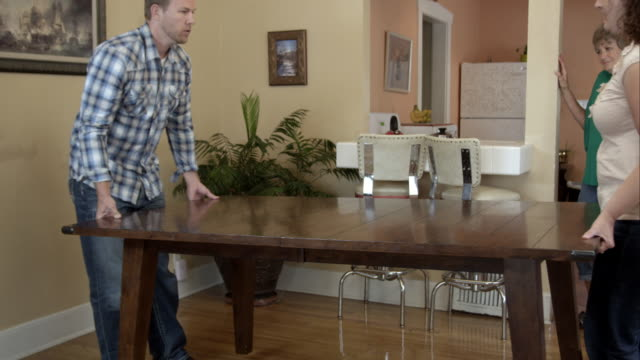 Young man and woman moving table for elderly woman.
