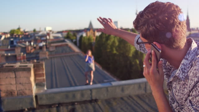 Young man and woman on an urban rooftop speak to each other on their phones