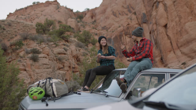 young man and woman on moab climbing trip sit on roof of car with gear and talk as they eat sandwiches. - ジープ点の映像素材/bロール