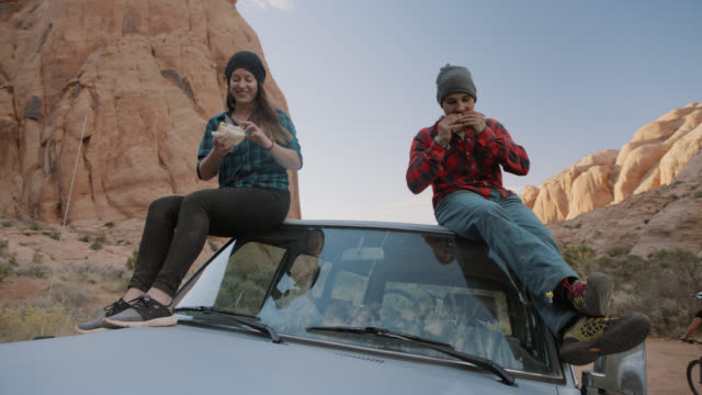 Young man and woman on Moab road trip sit on roof of car and eat sandwiches in rocky canyon.