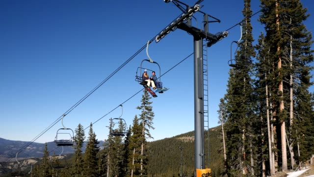 young man and woman on ski lift - seggiovia video stock e b–roll