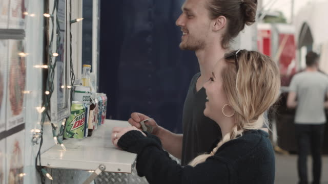 young man and woman ordering food at a food truck counter - ordering stock videos and b-roll footage