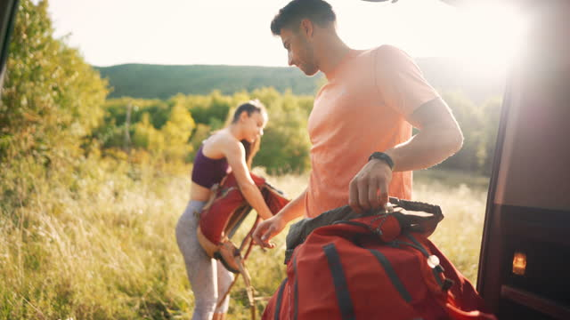 young man and woman packing climbing equipment and backpacks into the car trunk - climbing equipment stock videos & royalty-free footage